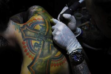 Tattoo artist Endless Sun works on a customer at Taipei International Tattoo & Music Festival