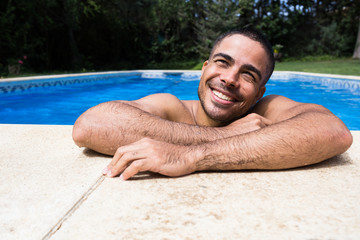 Smiling man dreaming while swimming in pool.
