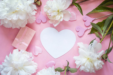 White peonies with empty heart-card, gift box and decorative hearts on a pink background.