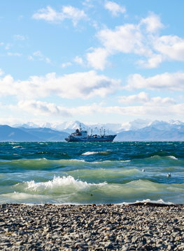 Seascape, ship floating away into the distance, mountains, sky, stones