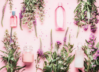 Natural cosmetic products setting with various bottles and fresh herbs and flowers on pink background, top view, flat lay. Beauty, skin, hair or body care concept Fototapete