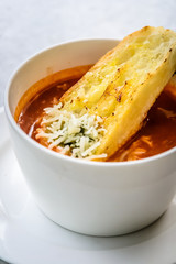 italian minestrone soup with garlic bread and grated cheddar cheese