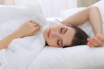 Beautiful young woman sleeping while lying in her bed and relaxing comfortably. It is easy to wake up for work or the day off. Concept of pleasant and rest reinstatement for active life