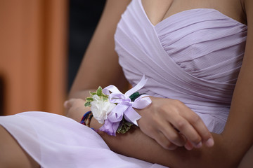 Close-up of young Caucasian woman, sitting down at a wedding ceremony and holding fingers into a nervous gesture