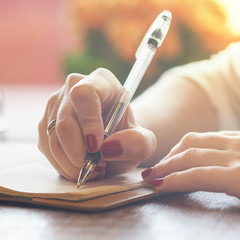 woman's hand with red nails writing some message note or letter to notebook by pen