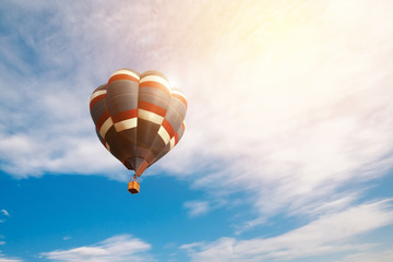 Travel and tourism concept. Colorful hot air balloon flying at sunrise with cloudy blue sky background