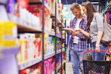 Young smiling couple discussing what to buy in supermarket