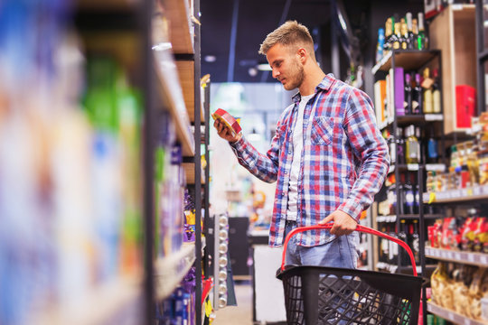 Young man shopping in a supermarket holding shopping cart