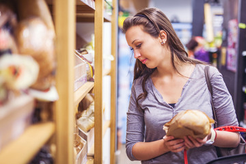 Young woman buying bread in a bakery section in supermarket