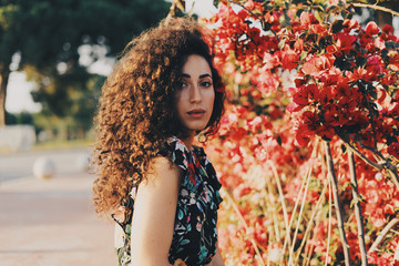 Beautiful caucasian female wearing colorful summer dress is looking at the camera while standing beside the flowers on a summer day. Brunette hipster girl with long curly hair is having rest outdoors.