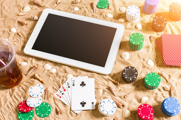 Online poker game on the beach with digital tablet and stacks of chips. Top view