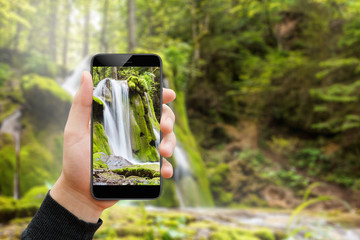Man hand holding smartphone and taking picture of waterfall