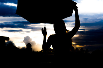 Silhouette of a girl on a sunset sky background playing with an umbrella