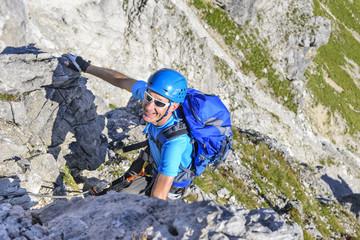 Mann klettert gutgelaunt im Klettersteig