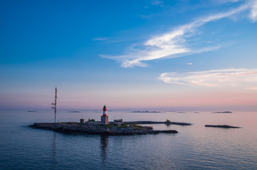 Pink sunset over the small island with a lighthouse near Helsinki Finland