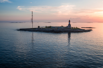 Harmaja lighthouse on a small isolated island nearby Helsinki archipelago teletower reflects in the water