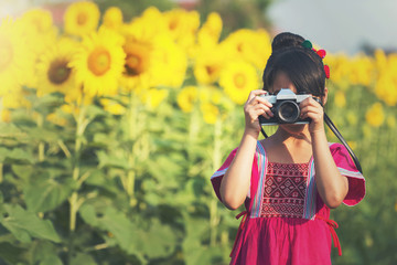 Portrait of cheerful smiling little girl making photo with camera in hands outdoors