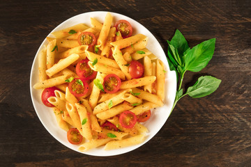 Penne pasta with tomato sauce and fresh basil leaves