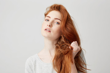 Close up of young beautiful ginger girl looking at camera touching hair over white background.