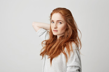 Portrait of young pretty ginger girl with freckles looking at camera touching hair over white background.