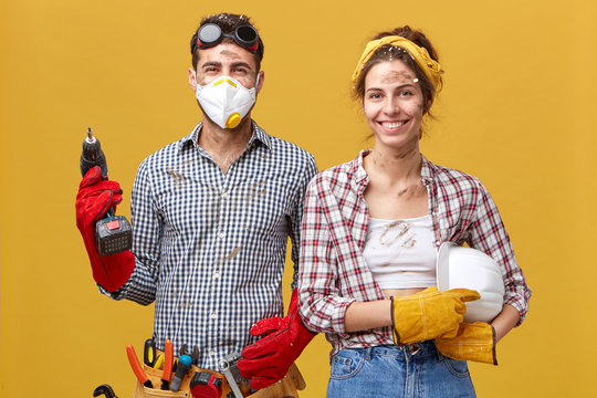 Studio portrait of cheerful male wearing protective mask, goggles and gloves holding drill fixing something at house and his wife who is helping him with construction holding hardhat. Service workers