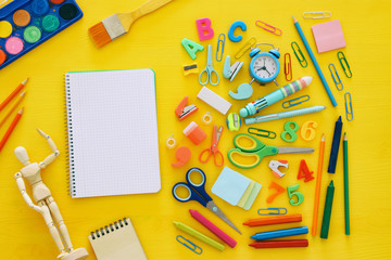 Back to school concept. Top view. School notebook on yellow wooden background