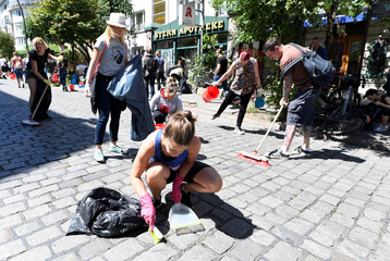"Residents clean the street during a ""Clean-up"" after demonstrations at the G20 summit in the Sternschanze district in Hamburg"
