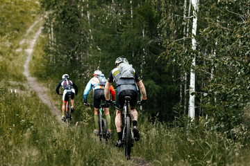 In de dag Fietsen group athletes cyclist mountainbike riding forest trail