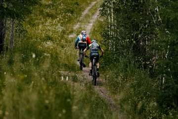 men cyclist on bicycles with backpacks mountain biking