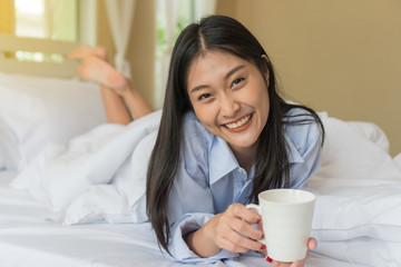 Happy smiling Asian young woman lying holding a cup of coffee on bed.