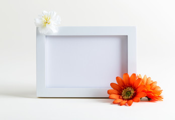 Blank white picture frame with flowers on a white background