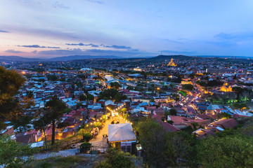 Sunset panorama view of Tbilisi, capital of Georgia country. Metekhi church, Holy Trinity Cathedral (Sameba), Presidential Administration, Bridge of Peace at night with illumination and moving cars.