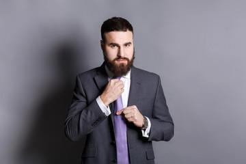 Handsome bearded businessman adjusting his tie