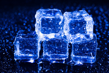 Ice cubes in blue light on black wet table.