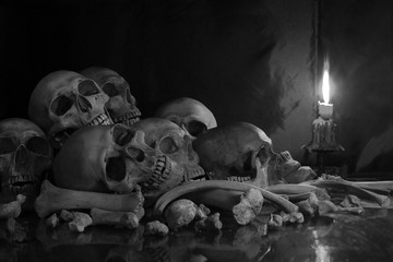 Pile of Skulls and bones on the reflection floor and old dirty wall have Lighting by candlelight