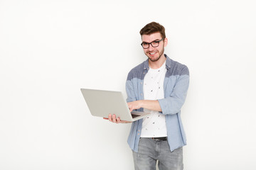 Young man standing with laptop
