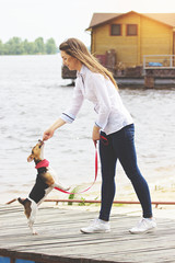Time to eat. Full-length side view shot of pretty and young woman in casual clothing giving bone to dog and smiling while playing with dog on pier.