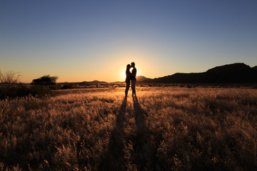 Couple kissing at african savanna landscape. Namibia, South of Africa.
