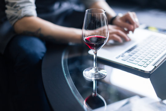 Portrait of senior sommelier sitting in front of laptop at wine cellar and tasting red wine while working together. Small business.