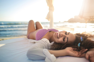 Attractive girl lying down on a bed in front of the sea