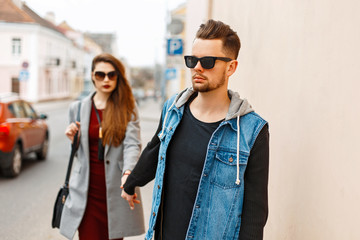 Beautiful stylish young couple with sunglasses in trendy clothes walking in the city. Lovers hands.