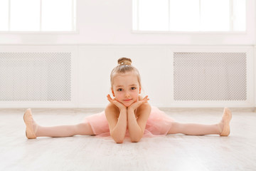 Portrait of little ballerina on floor, copy space