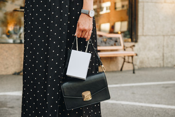 trendy young woman holding a small gift shopping bag and a chic black handbag on the city street. european blogger wearing a black and white polka dot dress and a watch. shopping concept.