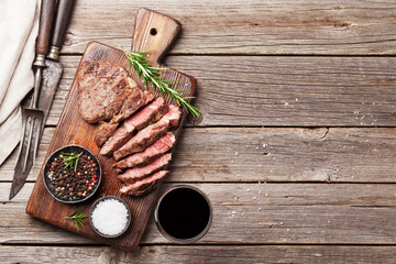Poster Grill / Barbecue Grilled beef steak with spices on cutting board