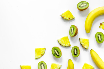 Concept of summer tropical fruits. Banana, kiwi, pineapple on white background top view copyspace