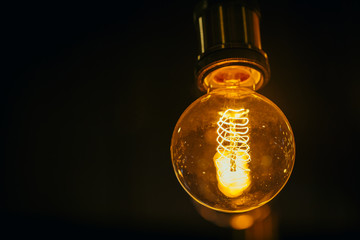 single light bulb on dark background with space for text.