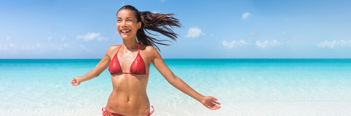Wall Mural - Summer vacation woman happy running on beach enjoying holidays travel. Banner panorama crop with ocean copyspace background. Bikini girl with open arms carefree, healthy lifestyle.