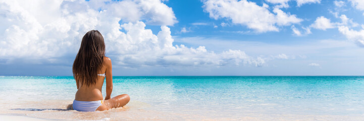 Wall Mural - Beach luxury travel vacation woman relaxing banner. Panorama background summer spa retreat resort sitting enjoying ocean view meditating. Wellness relaxation holiday.
