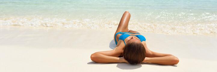 Wall Mural - Beach suntan vacation bikini woman lying down tanning under tropical sun in Caribbean. Sexy girl sunbathing banner. Panorama landscape of white sand travel summer holidays. Luxury wellness.