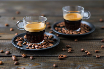 Two cups of espresso and coffee beans on a wooden table
